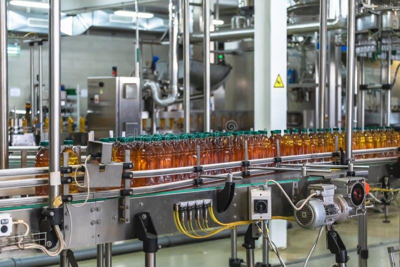 Πλαστικά μπουκάλια με το φρέσκο οργανικό χυμό στην αυτόματη ζώνη μεταφορέων ή τη γραμμή στο εσωτερικό εργοστασίων ή εγκαταστάσεων στοκ φωτογραφία