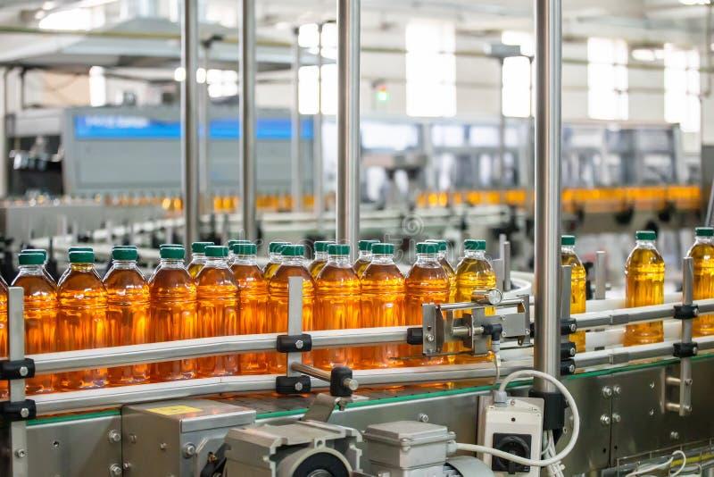 Πλαστικά μπουκάλια με το φρέσκο οργανικό χυμό στην αυτόματη ζώνη μεταφορέων ή τη γραμμή στο εργοστάσιο ή τις εγκαταστάσεις ποτών στοκ φωτογραφίες με δικαίωμα ελεύθερης χρήσης