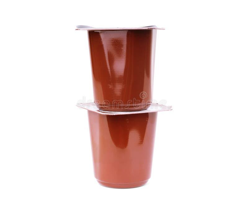 Πλαστικά φλυτζάνια με το γιαούρτι στο άσπρο υπόβαθρο στοκ εικόνα
