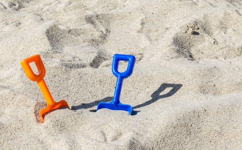 2 πλαστικά φτυάρια σε μια αμμώδη παραλία μια ηλιόλουστη θερινή ημέρα στοκ φωτογραφία