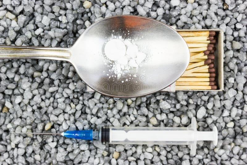 Πλαστική σύριγγα, ένα κουτάλι και μια αντιστοιχία στο λεπτό αμμοχάλικο στοκ εικόνες με δικαίωμα ελεύθερης χρήσης