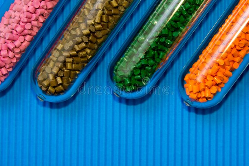 Πλαστικοί σβόλοι Πολυμερής χρωστική ουσία στους σωλήνες δοκιμής στο ζαρωμένο υπόβαθρο Χημικό υπόβαθρο με τους πλαστικούς σβόλους στοκ εικόνα