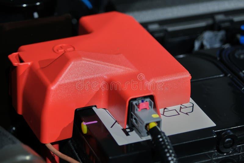 πλαστικό κάλυμμα του θετικού άκρου του κελιού της μπαταρίας με το κόκκινο σύμβολο συν, η μπαταρία τοποθετείται στο διαμέρισμα του στοκ εικόνες με δικαίωμα ελεύθερης χρήσης