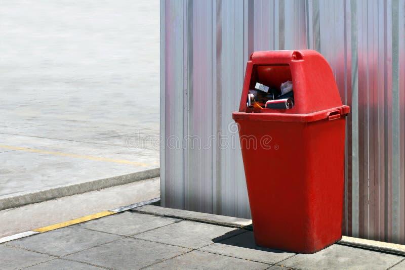 Πλαστικό, κόκκινο δοχείο δοχείων υπαίθρια στα φύλλα ψευδάργυρου τοίχων, κόκκινο δοχείων για τα ανακύκλωσης απόβλητα απορριμάτων,  στοκ εικόνα