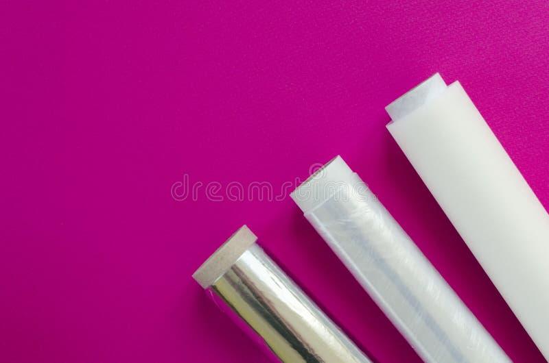 Πλαστικό περικάλυμμα, φύλλο αλουμινίου αργιλίου, έγγραφο περγαμηνής στο ρόδινο υπόβαθρο στοκ εικόνα με δικαίωμα ελεύθερης χρήσης