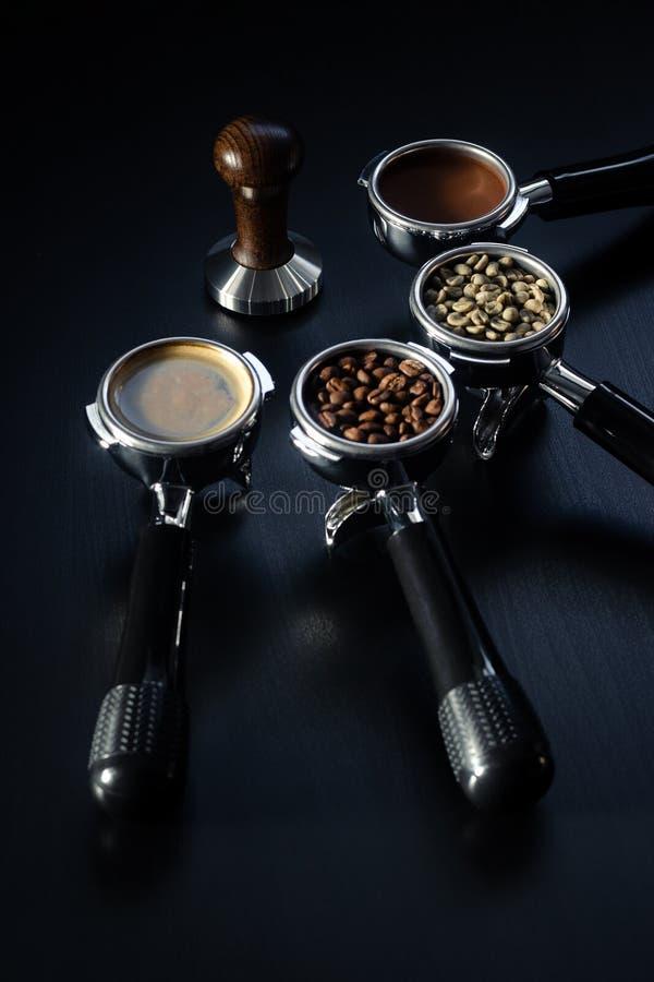 Πλαστογράφηση και τέσσερις κάτοχοι φίλτρων espresso γέμισαν με τα πράσινα, ψημένα, φασόλια εδάφους και έτοιμος καφές espresso στο στοκ εικόνα