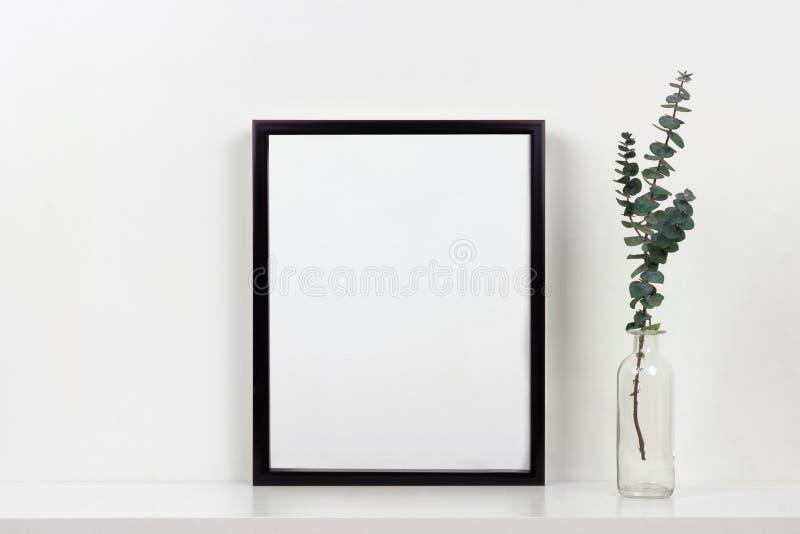 Πλαστό επάνω μαύρο πλαίσιο ενάντια στον άσπρο τοίχο με το βάζο των κλάδων σε ένα άσπρο ράφι στοκ φωτογραφίες