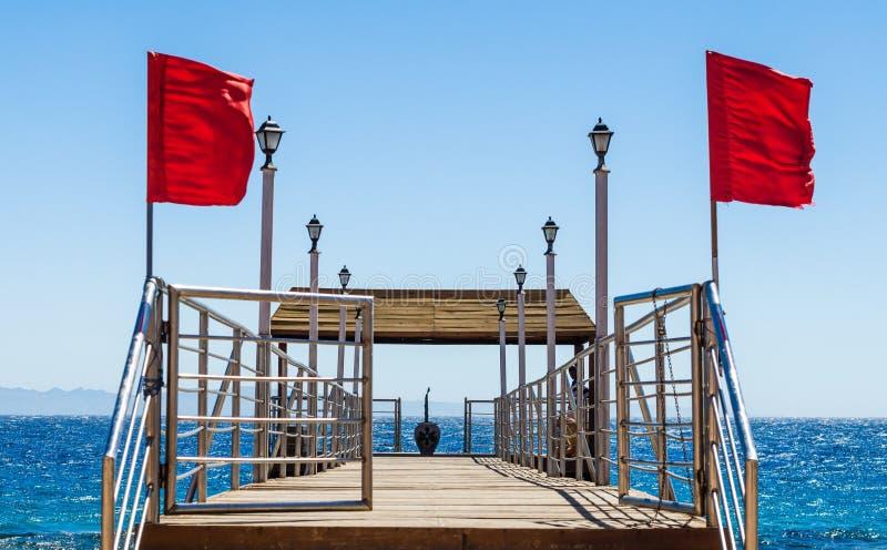 Πλατφόρμα στην παραλία με τα φανάρια και κόκκινες σημαίες στο υπόβαθρο της θάλασσας στην Αίγυπτο στοκ φωτογραφίες
