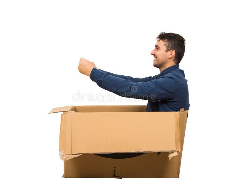Πλαϊνή όψη σε όλο το μήκος ενός παιδού που κάθεται μέσα σε ένα χάρτινο κουτί προσποιούμενος ότι οδηγεί ένα νέο αυτοκίνητο απομονω στοκ φωτογραφία με δικαίωμα ελεύθερης χρήσης