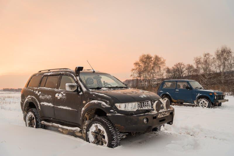 Πλαϊνός αθλητισμός Montero και Lada Niva 4x4 VAZ 2121/21214 της Mitsubishi Pajero αυτοκινήτων που σταθμεύουν στον τομέα χιονιού στοκ φωτογραφίες