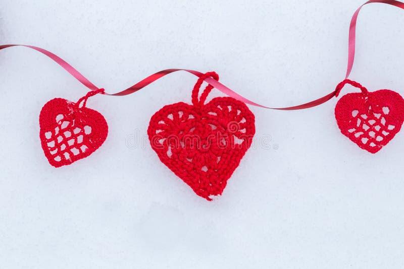 Πλεγμένες κόκκινες καρδιές με την κορδέλλα στο χιόνι Ανασκόπηση ημέρας βαλεντίνων στοκ εικόνα