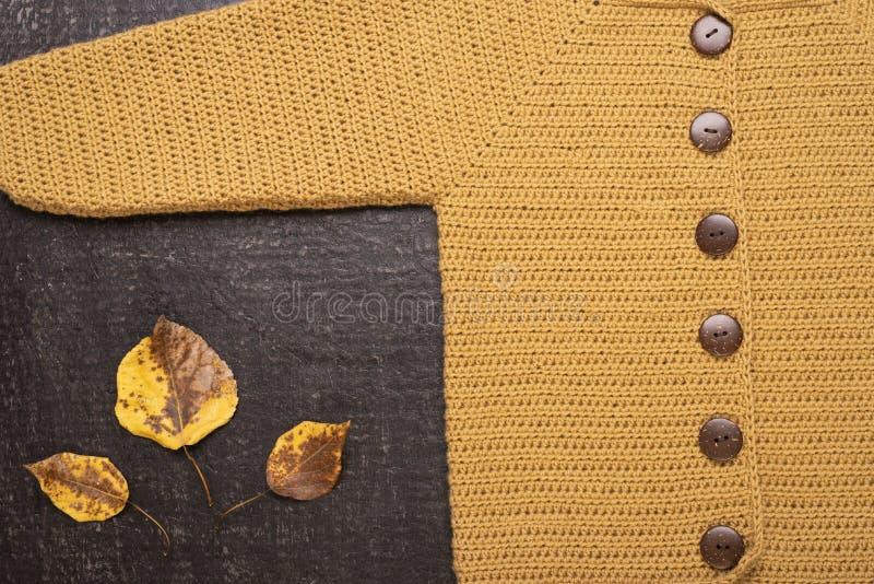 Πλεγμένη κίτρινη ζακέτα σε ένα μαύρο υπόβαθρο στοκ φωτογραφία με δικαίωμα ελεύθερης χρήσης