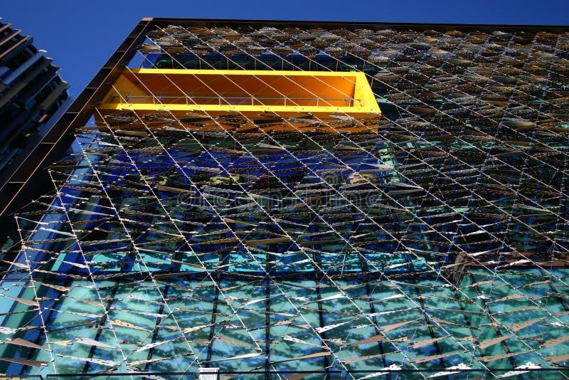 Πλεγμένη οθόνη προσόψεων μπροστά από τα παράθυρα γυαλιού και τα κίτρινα πλαισιωμένα μπαλκόνια στοκ εικόνα με δικαίωμα ελεύθερης χρήσης