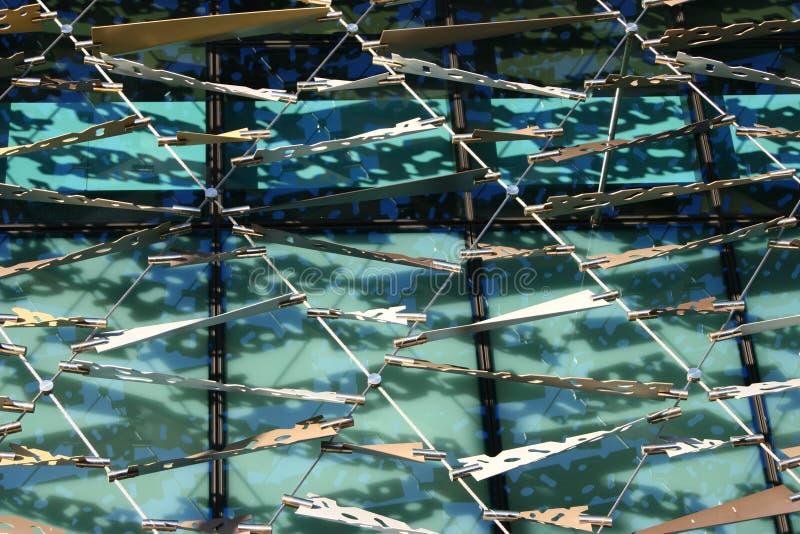 Πλεγμένη οθόνη προσόψεων μπροστά από τα παράθυρα γυαλιού με τις σκιές φυλλώματος στοκ εικόνες
