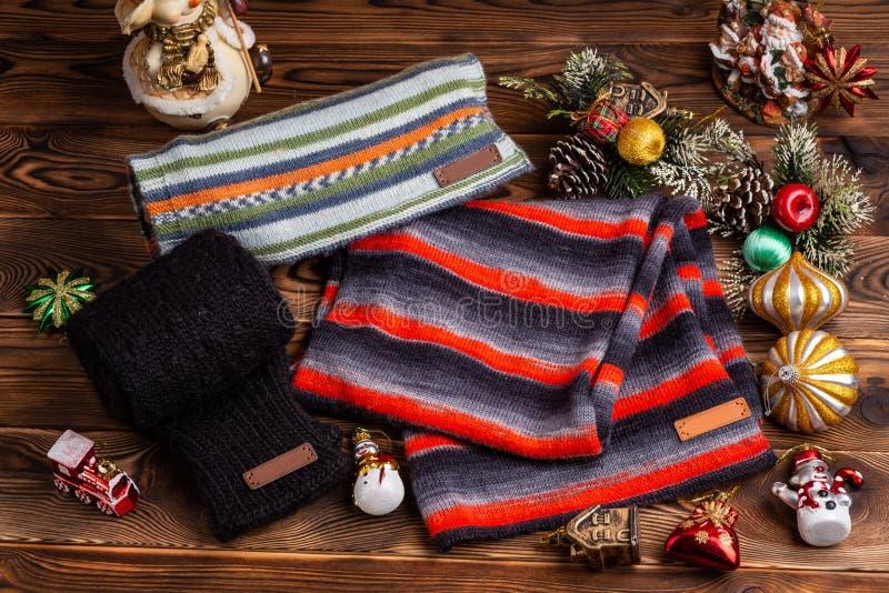 Πλεκτά ριγωτά ριγωτά μαντίλι, μαύρα πλεκτά μανίκια και παιχνίδια Χριστουγέννων στο ξύλινο υπόβαθρο στοκ εικόνες με δικαίωμα ελεύθερης χρήσης