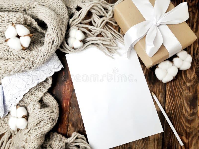 Πλεκτό μαντίλι, κιβώτιο δώρων και κενό κενό εγγράφου στο ξύλινο υπόβαθρο στοκ εικόνες