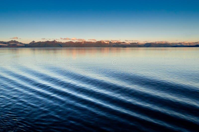 Πλευρά λιμένων κυματισμών κυμάτων τόξων σκαφών και αναμμένα αυγή βουνά στο υπόβαθρο Αλάσκα, ΗΠΑ στοκ φωτογραφία με δικαίωμα ελεύθερης χρήσης