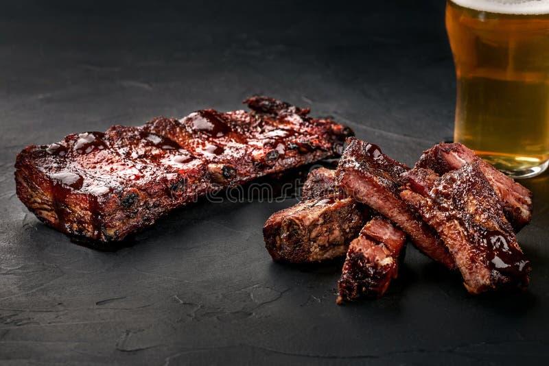Πλευρά χοιρινού κρέατος στη σάλτσα σχαρών και ένα ποτήρι της μπύρας σε ένα μαύρο πιάτο πλακών Ένα μεγάλο πρόχειρο φαγητό στην μπύ στοκ φωτογραφία