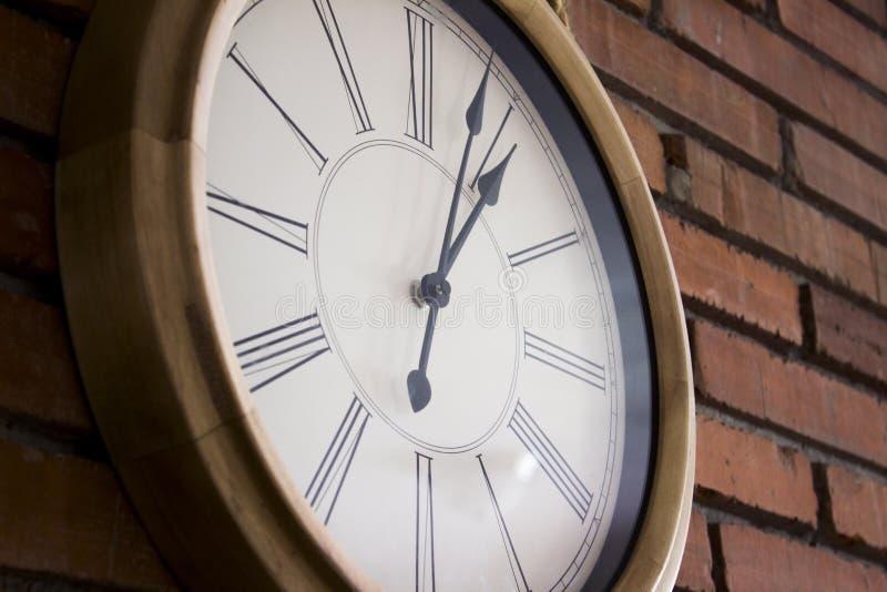Πλευρά close†«επάνω ενός ξύλινου ρολογιού τοίχων με τους ρωμαϊκούς αριθμούς που κρεμά σε έναν τούβλινο τοίχο στοκ φωτογραφίες