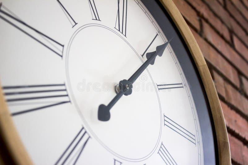 Πλευρά close†«επάνω ενός ξύλινου ρολογιού τοίχων με τους ρωμαϊκούς αριθμούς που κρεμά σε έναν τούβλινο τοίχο στοκ φωτογραφία με δικαίωμα ελεύθερης χρήσης