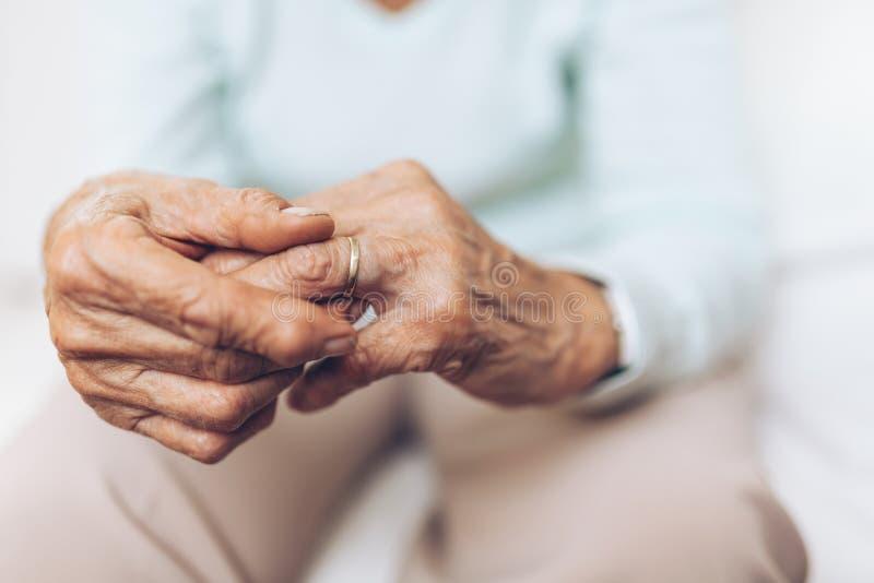 Πληγωμένη ηλικιωμένη γυναίκα που κρατά ένα γαμήλιο δαχτυλίδι στοκ φωτογραφίες