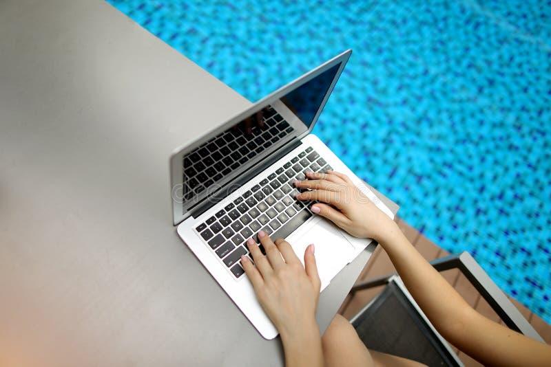 Πληκτρολόγιο συμπίεσης χεριών γυναικών άποψης άνωθεν στενό επάνω στην ηλιόλουστη πισίνα ημέρας lap-top στοκ φωτογραφία