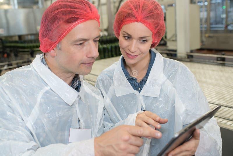 Πληροφορίες ανάγνωσης ζυθοποιείων εργαζομένων από την ταμπλέτα στοκ εικόνες