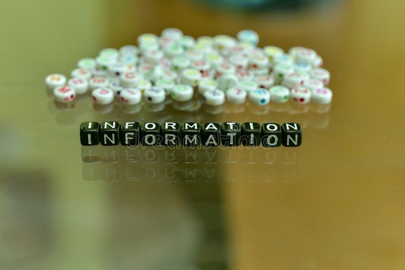 ΠΛΗΡΟΦΟΡΙΕΣ που γράφονται με τον ακρυλικό μαύρο κύβο με τις άσπρες χάντρες αλφάβητου για το υπόβαθρο γυαλιού στοκ εικόνα
