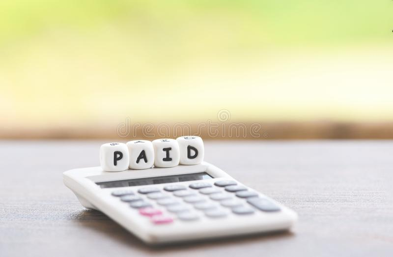 Πληρωμένες λέξεις και υπολογιστής στον πίνακα για πληρωμένη τη χρόνος πληρωμή στην επιχείρηση γραφείων στοκ εικόνες με δικαίωμα ελεύθερης χρήσης