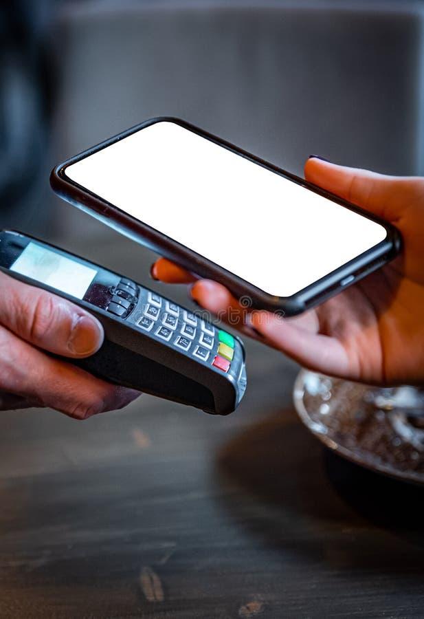 Πληρωμή χωρίς επαφές για κινητές συσκευές Πληρωμή μέσω κινητού σε καφετέρια με έξυπνο τηλέφωνο στοκ φωτογραφία με δικαίωμα ελεύθερης χρήσης