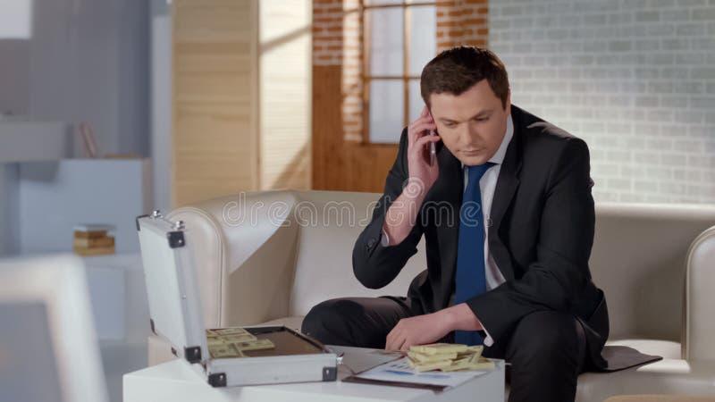 Πλούσιος άνθρωπος που εξετάζει το συνεργάτη τηλεφωνικώς, μεγάλα χρήματα στον πίνακα, κερδοφόρα επιχείρηση στοκ φωτογραφίες