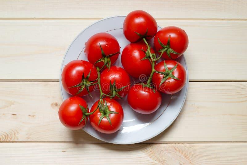 Πλυμένες κόκκινες ωριμασμένες ντομάτες κερασιών στο άσπρο πιάτο στον ελαφρύ ξύλινο πίνακα στοκ φωτογραφίες