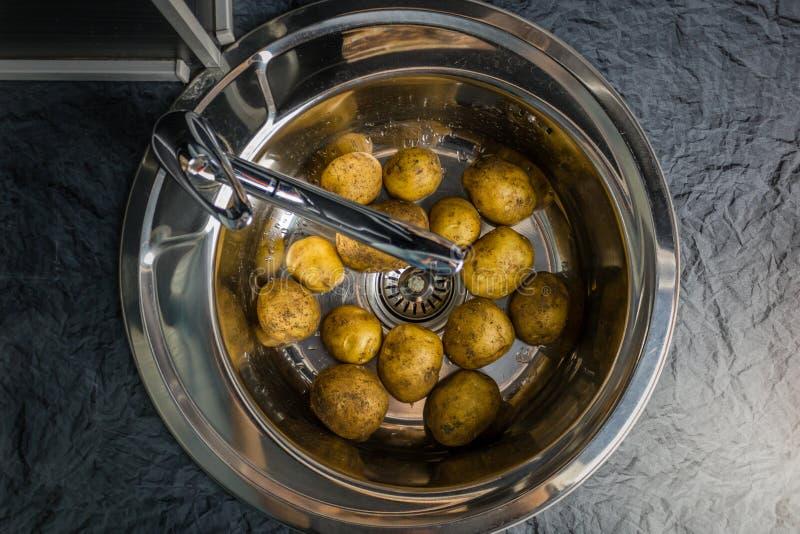 Πλύντε τις ακατέργαστες πατάτες στο νεροχύτη Συμβολίζει το αγροτικό εγχώριο μαγείρεμα στοκ φωτογραφίες με δικαίωμα ελεύθερης χρήσης