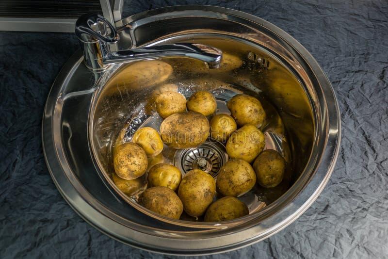 Πλύντε τις ακατέργαστες πατάτες στο νεροχύτη Συμβολίζει το αγροτικό εγχώριο μαγείρεμα στοκ φωτογραφία με δικαίωμα ελεύθερης χρήσης