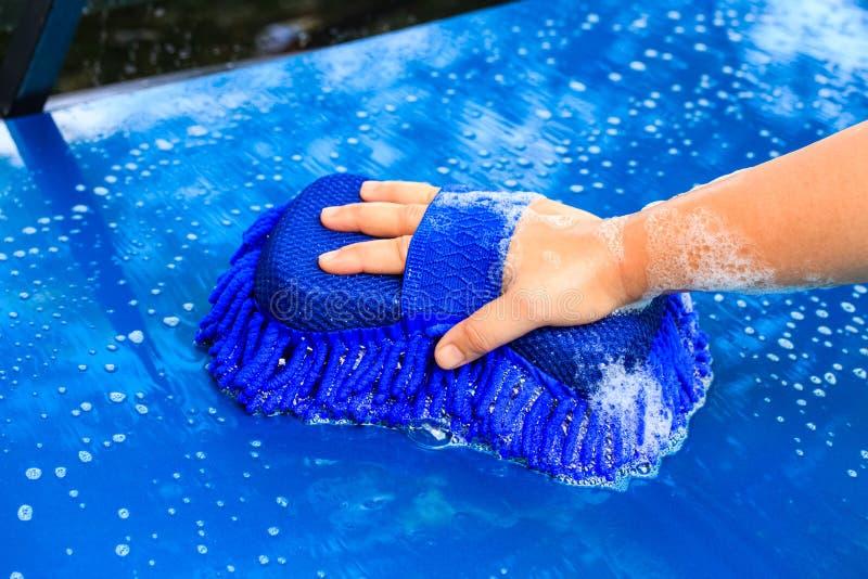Πλύσιμο ενός αυτοκινήτου με το μπλε σφουγγάρι και το σαπούνι στοκ εικόνα με δικαίωμα ελεύθερης χρήσης