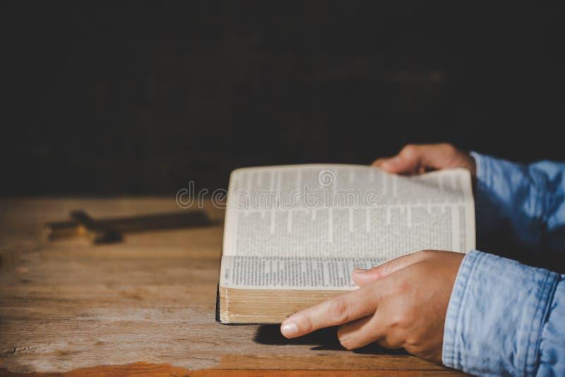 Πνευματικότητα και θρησκεία, χέρια που διπλώνονται στην προσευχή σε μια ιερή Βίβλο στοκ εικόνες