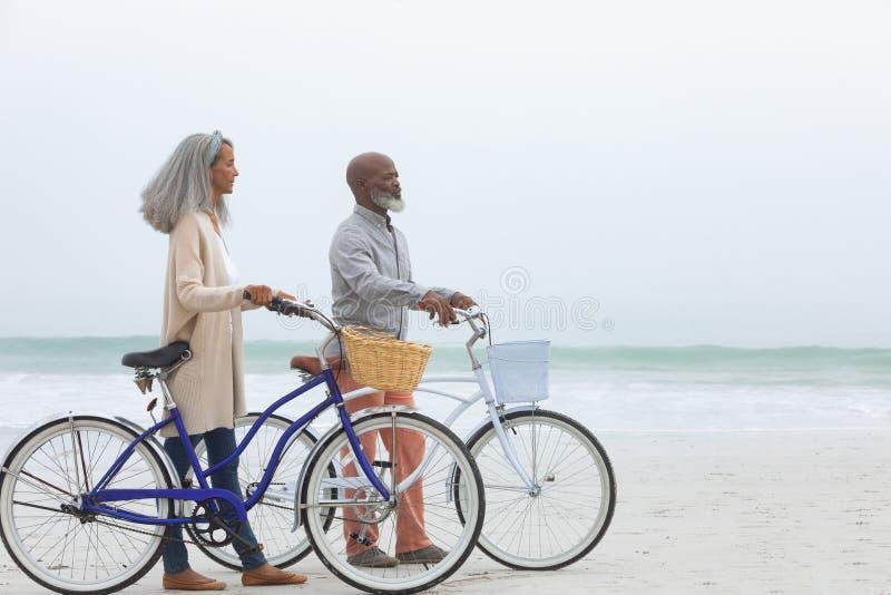 Ποδήλατα εκμετάλλευσης ζεύγους από την παραλία στοκ εικόνες