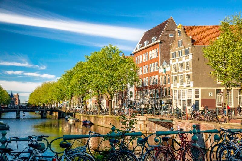 Ποδήλατα στη γέφυρα του Άμστερνταμ, Κάτω Χώρες έναντι καναλιού και παλαιών κτιρίων κατά τη θερινή ηλιόλουστη ημέρα Ταχυδρομική κά στοκ εικόνες