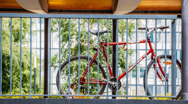 Ποδήλατο που κλειδώνεται στο κιγκλίδωμα με δύο κλειδαριές στοκ εικόνα με δικαίωμα ελεύθερης χρήσης
