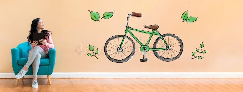Ποδήλατο Eco με τη γυναίκα που χρησιμοποιεί μια ταμπλέτα στοκ εικόνες