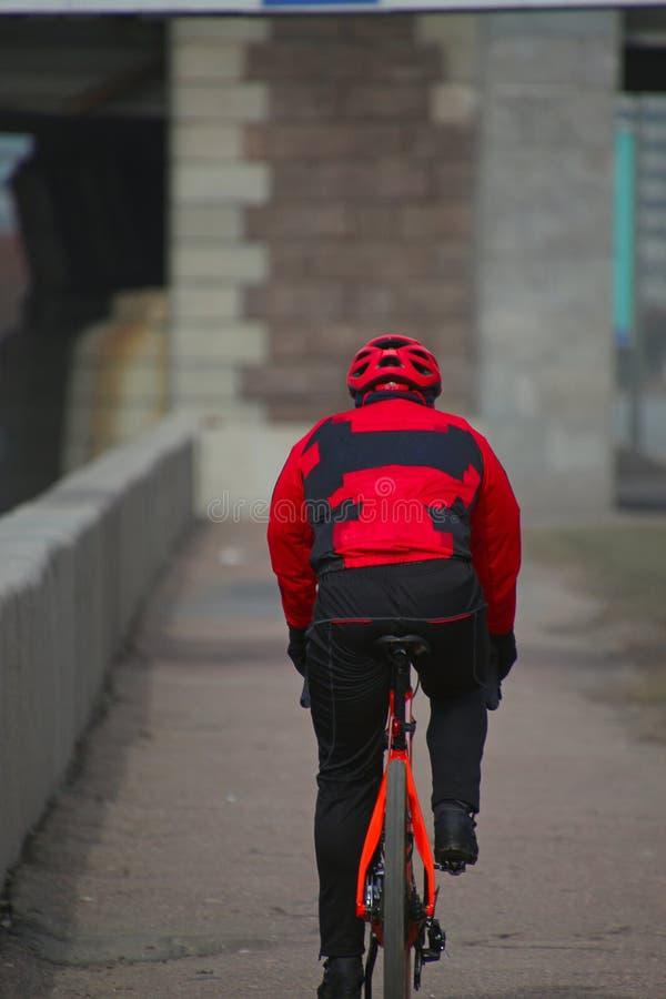 Ποδηλάτης γύρους στους κόκκινους φορμών γυμναστικής κατά μήκος του αναχώματος στοκ φωτογραφίες με δικαίωμα ελεύθερης χρήσης