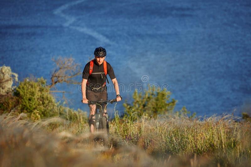 Ποδηλάτης με το σακίδιο πλάτης στο ταξίδι ποδηλάτων βουνών του στην ακτή Ο ταξιδιώτης έχει adventur στο λιβάδι στην όχθη ποταμού στοκ φωτογραφία με δικαίωμα ελεύθερης χρήσης