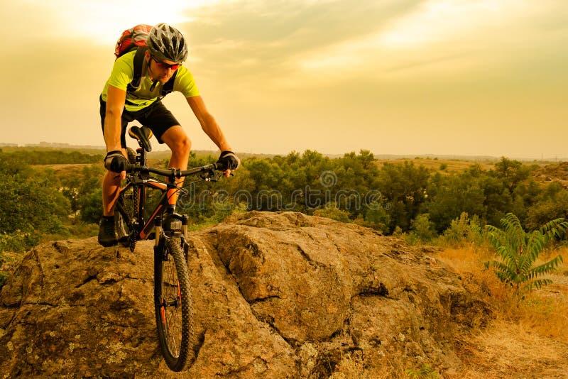 Ποδηλάτης που οδηγά το ποδήλατο στο δύσκολο ίχνος φθινοπώρου στο ηλιοβασίλεμα Ακραίος αθλητισμός και έννοια Enduro Biking στοκ εικόνα