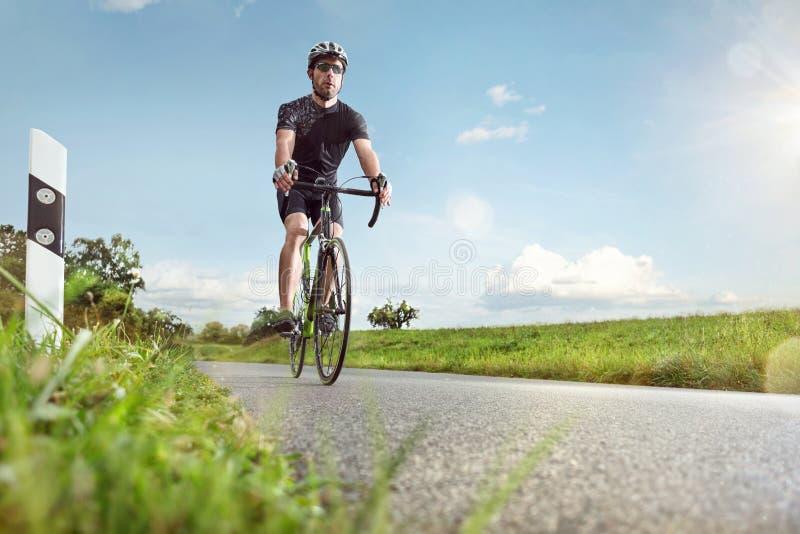 Ποδηλάτης σε έναν ηλιόλουστο δρόμο στοκ φωτογραφία με δικαίωμα ελεύθερης χρήσης