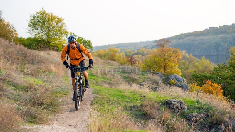 Ποδηλάτης στο πορτοκάλι που οδηγά το ποδήλατο βουνών στο δύσκολο ίχνος φθινοπώρου Ακραίος αθλητισμός και έννοια Enduro Biking στοκ φωτογραφίες