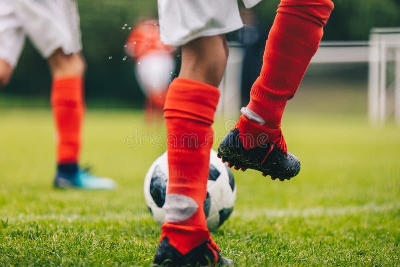 Ποδοσφαιριστές που κλωτσούν τη σφαίρα στον τόπο συναντήσεως χλόης Στάδιο πισσών ποδοσφαίρου στο υπόβαθρο στοκ φωτογραφίες με δικαίωμα ελεύθερης χρήσης