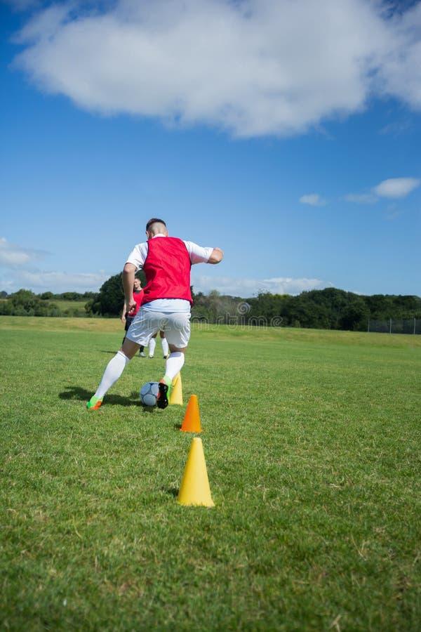 Ποδοσφαιριστής που στάζει μέσω των κώνων στοκ εικόνες