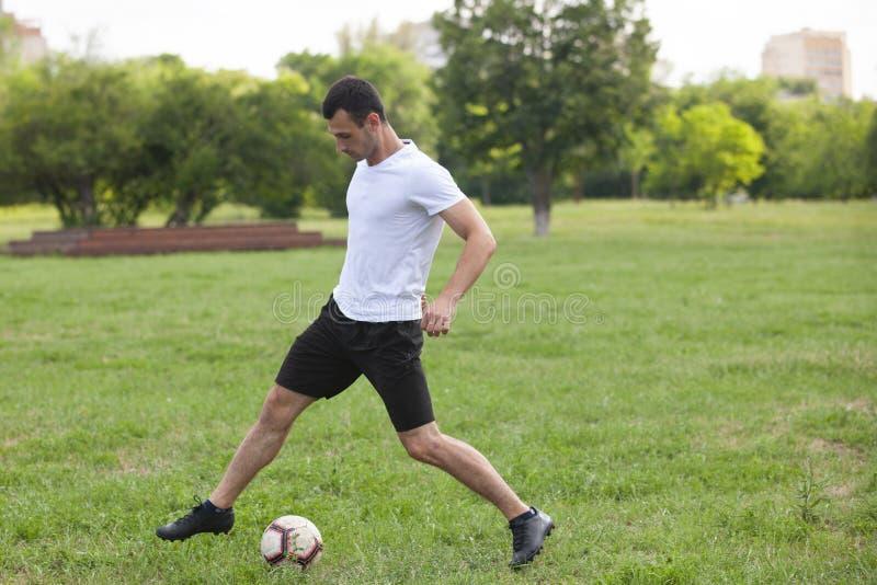 Ποδοσφαιριστής στη δράση Λάκτισμα ενός ποδοσφαίρου στοκ εικόνες
