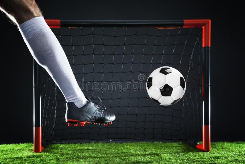 ποδόσφαιρο Έννοια πρωταθλήματος με τον ποδοσφαιριστή Πυροβολισμός απεργών στο στόχο στοκ εικόνα