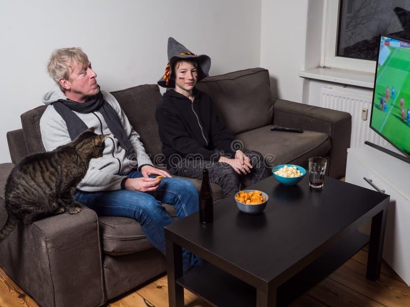 Ποδόσφαιρο Παγκόσμιου Κυπέλλου ποδοσφαίρου προσοχής πατέρων, γιων και γατών στη TV στοκ φωτογραφία με δικαίωμα ελεύθερης χρήσης